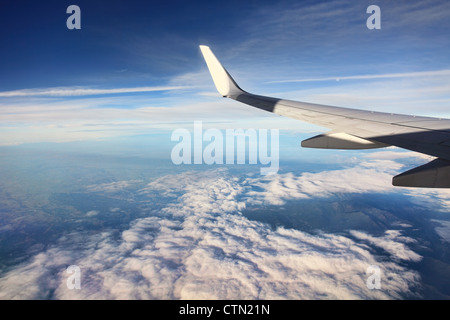 Aerial view on white clouds from airplane (wing view). - Stock Photo