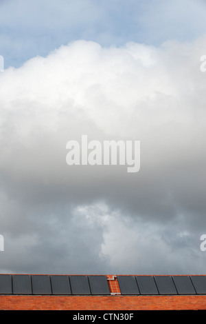 Solar panels on the roof of a building on a cloudy day - Stock Photo