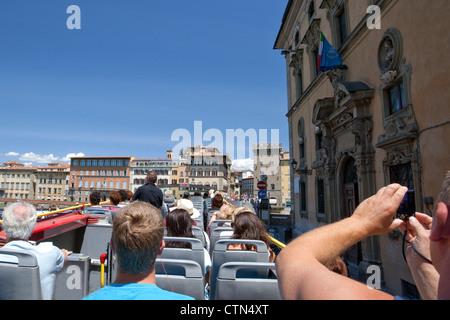 Tourist takes photo from open top of sightseeing bus, Florence, Italy - Stock Photo