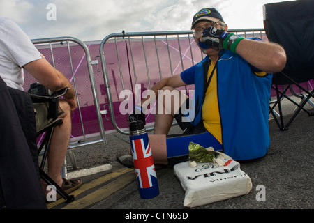 Spectators sips hot tea from a thermos flask on the first day of competition of the London 2012 Olympic 250km mens' - Stock Photo