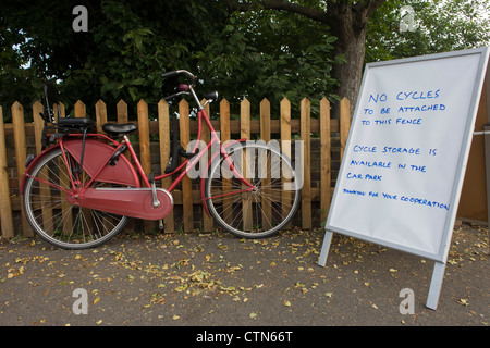 Spectator's bike locked up on a picket fence next to sign asking bicycles to be stored nearby at the local station - Stock Photo