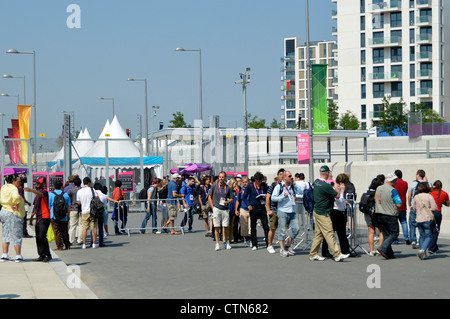 Queue at security check in entry point for media & press at 2012 Olympic Park with athletes village beyond EDITORIAL - Stock Photo