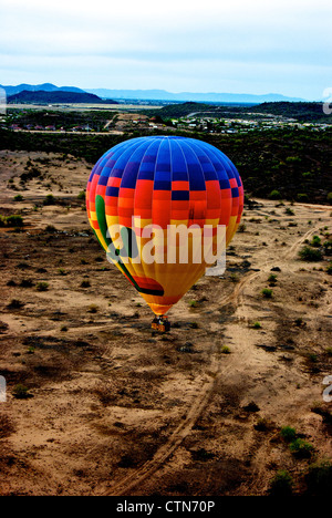 Hot Air Expeditions balloon floating over Sonoran Desert landscape Scottsdale AZ just after sunrise - Stock Photo