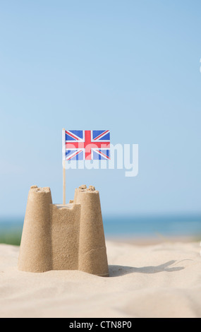 Union Jack flag in a sandcastle on the beach. Wells next the sea. Norfolk, England - Stock Photo