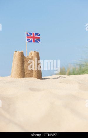Union Jack flag in a sandcastle on sand dunes. Wells next the sea. Norfolk, England - Stock Photo
