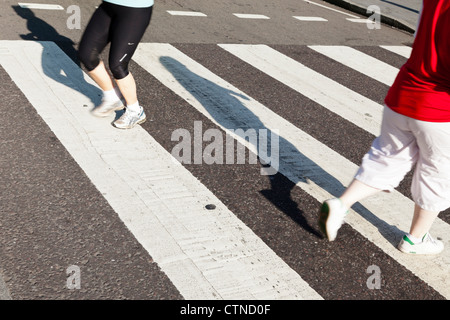 People running or jogging across a road using a zebra crossing, England, UK - Stock Photo