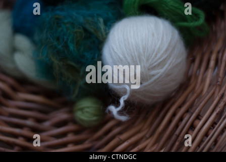 Close up of balls of wool in shades of green, white and beige in a willow basket. - Stock Photo