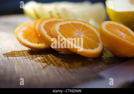 Slices of freshly cut orange on an oak board with out of focus melon in background. - Stock Photo