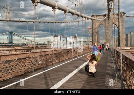 Tourists taking photos on the Brooklyn Bridge - Stock Photo