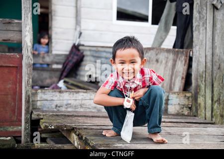 Smiling boy in water village (Kampong Ayer) Bandar Seri Begawan Brunei Borneo Asia. - Stock Photo