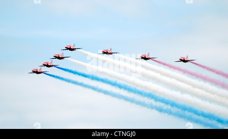 RAF Red Arrows display team trailing red, white and blue smoke - Stock Photo