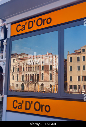 Ca' D'Oro vaporetto waterbus stop on Grand Canal with buildings across canal reflected in windows Cannaregio Venice - Stock Photo