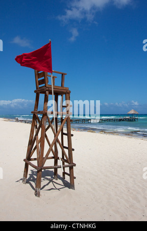 Empty lifeguard post with a red flag at a white, Caribbean beach under a clear sky. - Stock Photo