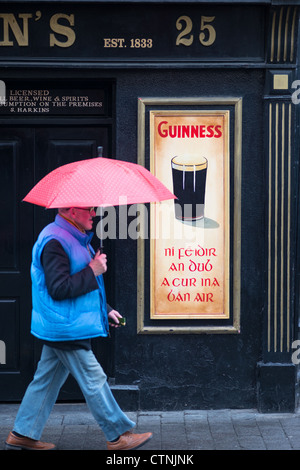 A man walks past a local pub in the rain in Kilkenny, Leinster, Republic of Ireland. - Stock Photo