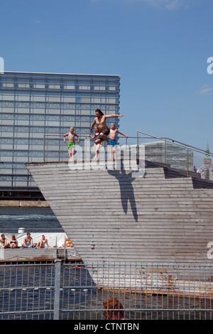 Young man jumping from the top of the diving tower in the Copenhagen Harbour Bath at Islands Brygge quay in Copenhagen - Stock Photo