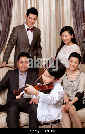 Little boy playing violin in front of family members - Stock Photo