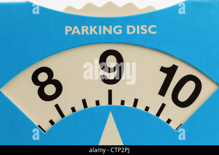 Cardboard parking disc arrival time indicator set at 9 am in the morning - Stock Photo