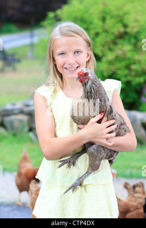 Young Blond Girl in the Garden with Chickens in a Yellow Dress - Stock Photo
