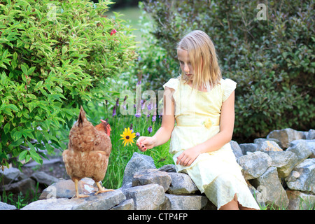 Young Blond Girl in the Garden Holding a Flower with Chickens in a Yellow Dress - Stock Photo