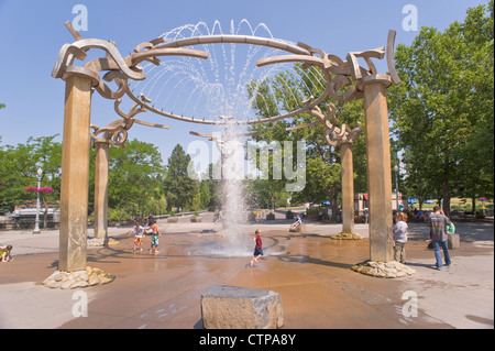 On a hot day kids and adults enjoy the cooling spray of the water fountain at Riverfront Park, in Spokane, Washington, - Stock Photo