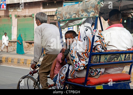 Cycle rickshaw with old driver transporting family as urban transport in Mathura, Uttar Pradesh, India - Stock Photo