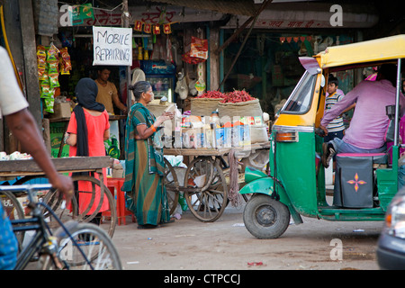 Mobile repair shop and three-wheeled taxi / bajaj in busy street in Delhi, India - Stock Photo