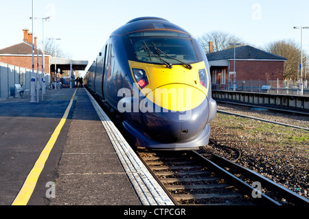 A high speed electric train stopped at a railway station - Stock Photo