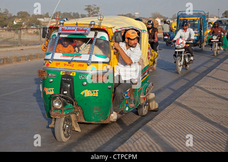 Fully loaded autorickshaw, three-wheeled motorized taxi in busy traffic at Agra, Uttar Pradesh, India - Stock Photo