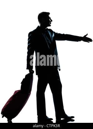 one caucasian man one caucasian business traveler man handshake  with suitcase  full length silhouette in studio - Stock Photo