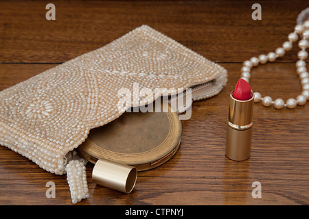 Vintage purse with antique powder compact, open bright red lipstick and a string of pearls on oak dressing table. - Stock Photo