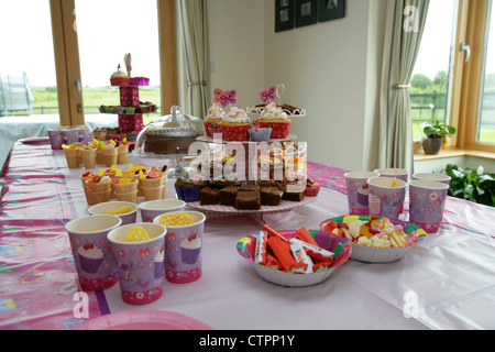 food and drink laid out on a table for a young girls birthday party - Stock Photo