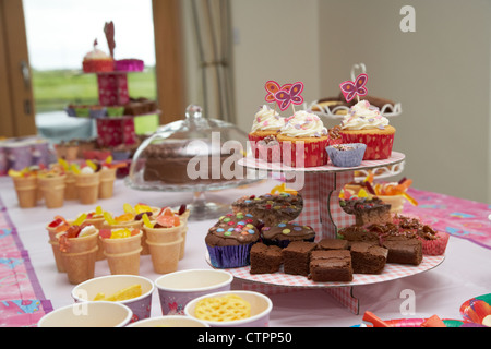 decorated cup cakes on a stand with food and drink laid out on a table for a young girls birthday party - Stock Photo