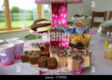 home made buns and cakes with food and drink laid out on a table for a young girls birthday party - Stock Photo