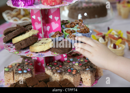 childs hand reaching out for a cookie food and drink laid out on a table for a young girls birthday party - Stock Photo