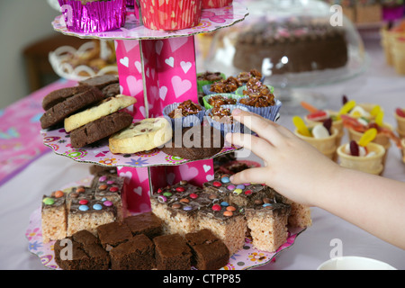 childs hand reaching out for food and drink laid out on a table for a young girls birthday party - Stock Photo