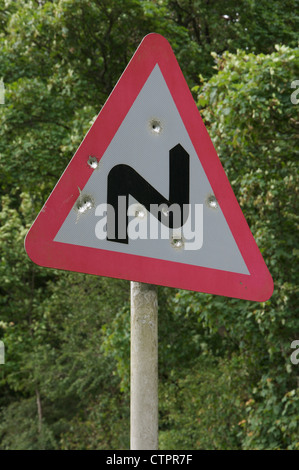 A British road sign warning of a double bend ahead. This one in rural Dorset has been shot at and peppered with - Stock Photo