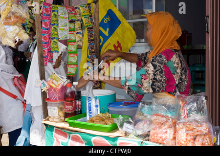 young muslim schoolgirl buying snacks at stall during break time java indonesia - Stock Photo