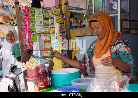 young muslim schoolboy buying snacks at stall during break time java indonesia - Stock Photo
