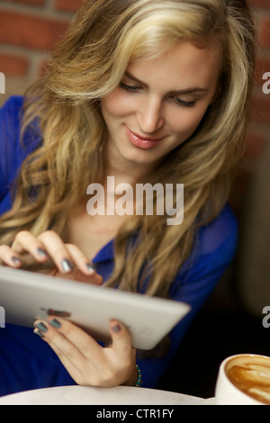 Beautiful smiling young woman reading from her ipad while enjoying her cappuccino at a coffee shop - Stock Photo