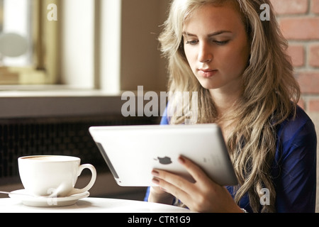 Beautiful young woman reading from her ipad while enjoying her cappuccino at a coffee shop - Stock Photo