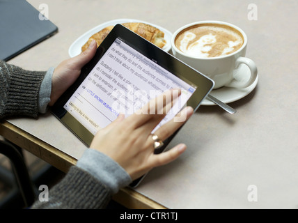 Close up picture of a female reading her newsfeed from an ipad - Stock Photo