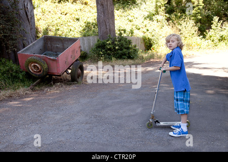 Boy outside playing on his scooter. - Stock Photo