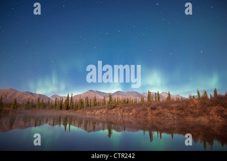 Northern Lights dancing over Alaska Range reflected in beaver pond along Parks Highway under full moon Broad Pass - Stock Photo