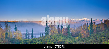 The early morning sun lights up Mount McKinley Alaska range as fog covers Chulitna River valley photographed Denali - Stock Photo