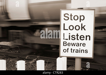 Beware of trains sign and speeding train at pedestrian crossing point near Great Ayton, North Yorkshire, England, - Stock Photo