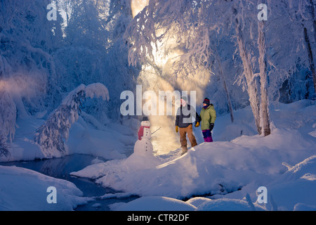 Husband wife standing in frosty forest next to snowman backlit by sunrays Russian Jack Springs Park Southcentral - Stock Photo