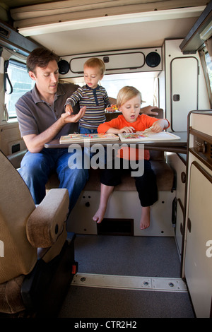 A father and his two sons are playing in the back of their camper trailer. - Stock Photo