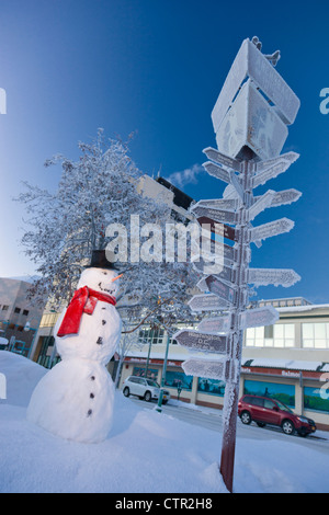 Snowman wearing black top hat red scarf standing next mileage signpost by visitors log cabin in downtown Anchorage - Stock Photo