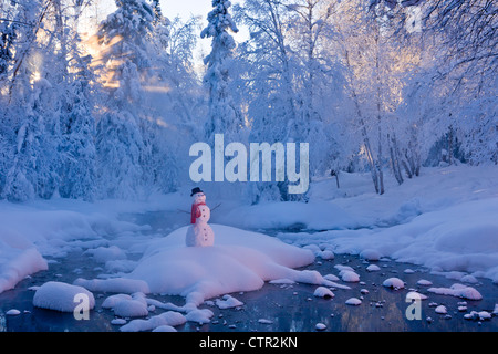 Snowman standing on small island in middle stream fog hoar frosted trees in background Russian Jack Springs Park - Stock Photo