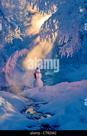 Snowman standing next stream sunrays shining through hoar frosted trees in background Russian Jack Springs Park - Stock Photo